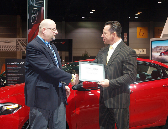 Randy hands off the 2012 Victory & Reseda Vehicle of The Year Award for the Dodge Dart to Reid Bigland at the 2013 Chicago Auto Show